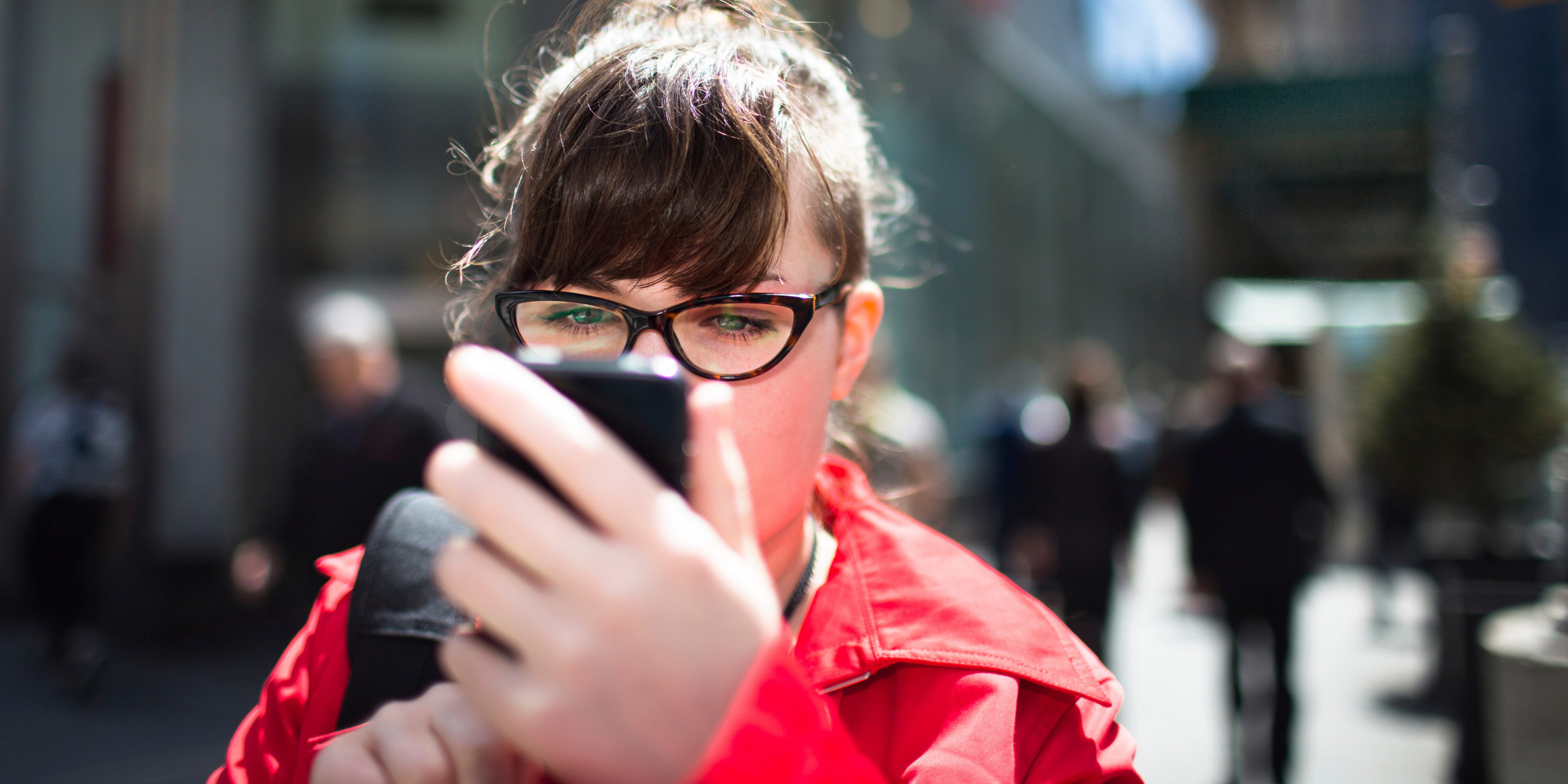 Woman on city street looking at smartphone